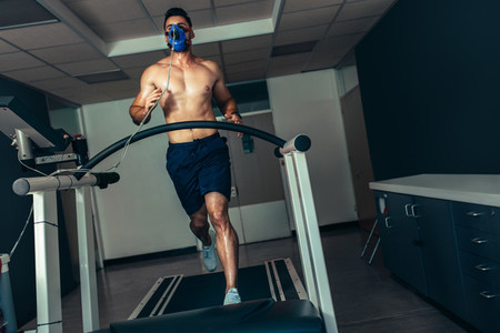 Runner with mask doing a performance test on treadmill