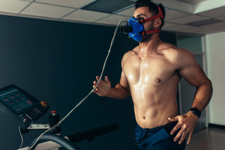 Fit and muscular athlete with mask running on treadmill
