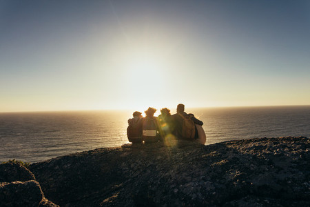 Friends admiring the sunset from mountain top