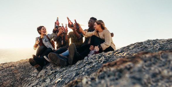 Friends sitting on mountain top and toasting beers