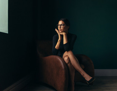 Beautiful young woman sitting on chair and looking away