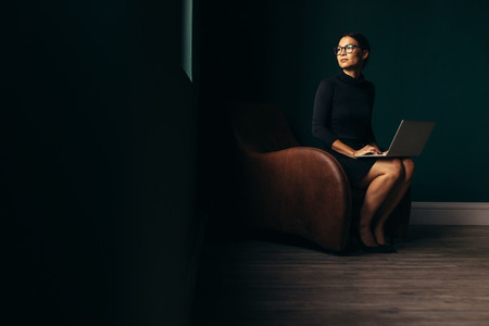 Thoughtful lady sitting on armchair with laptop