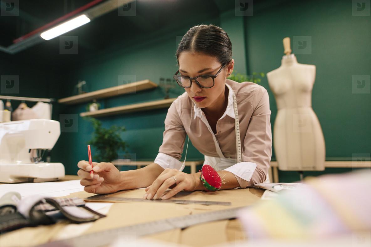 Dressmaker making a design draft on paper