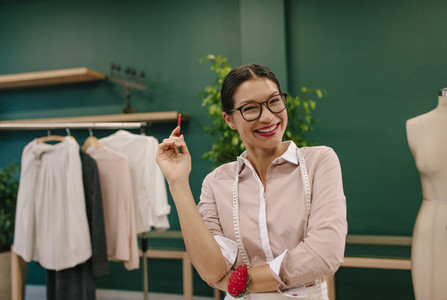 Smiling seamstress standing at her workshop