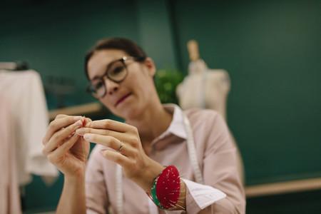 Female threading the needle at fashion studio