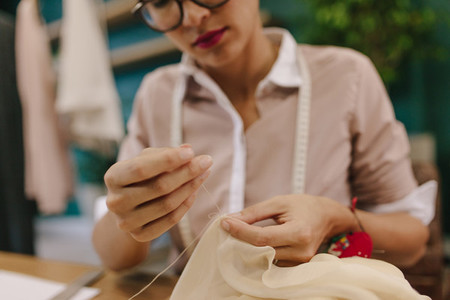 Woman hands doing handwork on dress