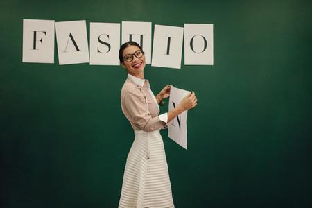 Female designer standing near wall with sticker