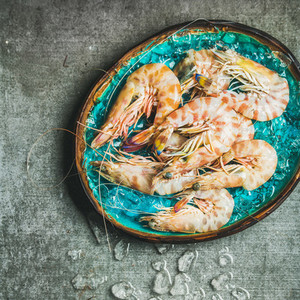 Raw uncooked tiger prawns on chipped ice copy space