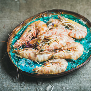 Raw uncooked tiger prawns on chipped ice in blue tray
