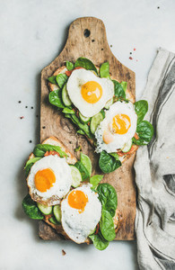 Healthy breakfast sandwiches on rustic wooden board top view