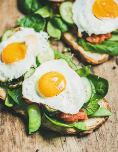 Healthy breakfast sandwiches on wooden board background