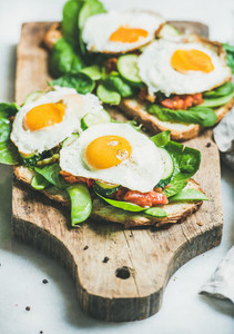 Bread toasts with fried eggs and fresh vegetables on board