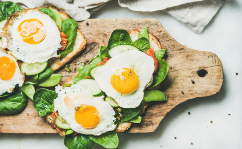 Healthy breakfast sandwiches with fried eggs and fresh vegetables
