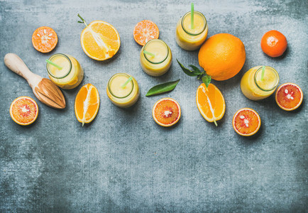 Healthy yellow smoothie in bottles over concrete background  top view