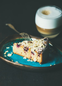 Piece of cake and glass of latte over dark background