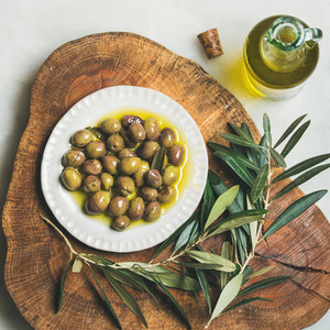 Pickled green Medoterranean olives and olive tree branch on wooden board