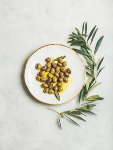 Pickled green Mediterranean olives in virgin olive oil on plate