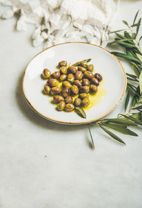 Pickled green Mediterranean olives in olive oil on white plate
