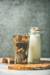 Glass with frozen coffee ice cubes and milk in bottle