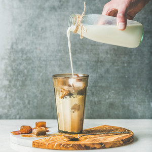 Mans hand pouring milk to Iced latte summer coffee cocktail