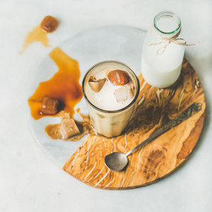 Iced caramel latte coffee cocktail with milk and coffee cubes