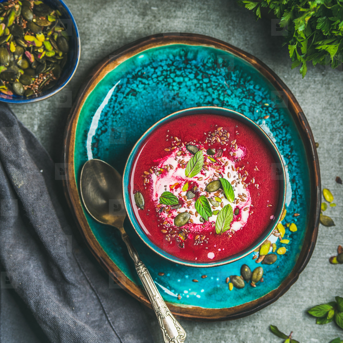 Spring beetroot soup on bright blue plate over gery background