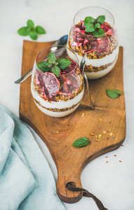Healthy breakfast glasses with yogurt and granola on wooden board