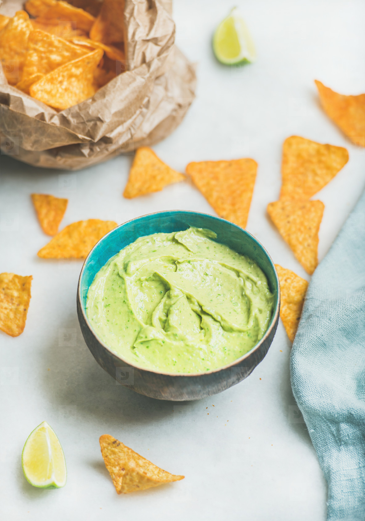 Mexican corn chips and fresh guacamole sauce over marble background