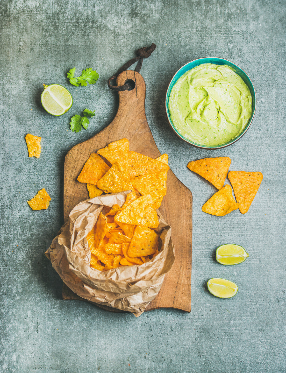 Mexican corn chips and fresh guacamole sauce on wooden board