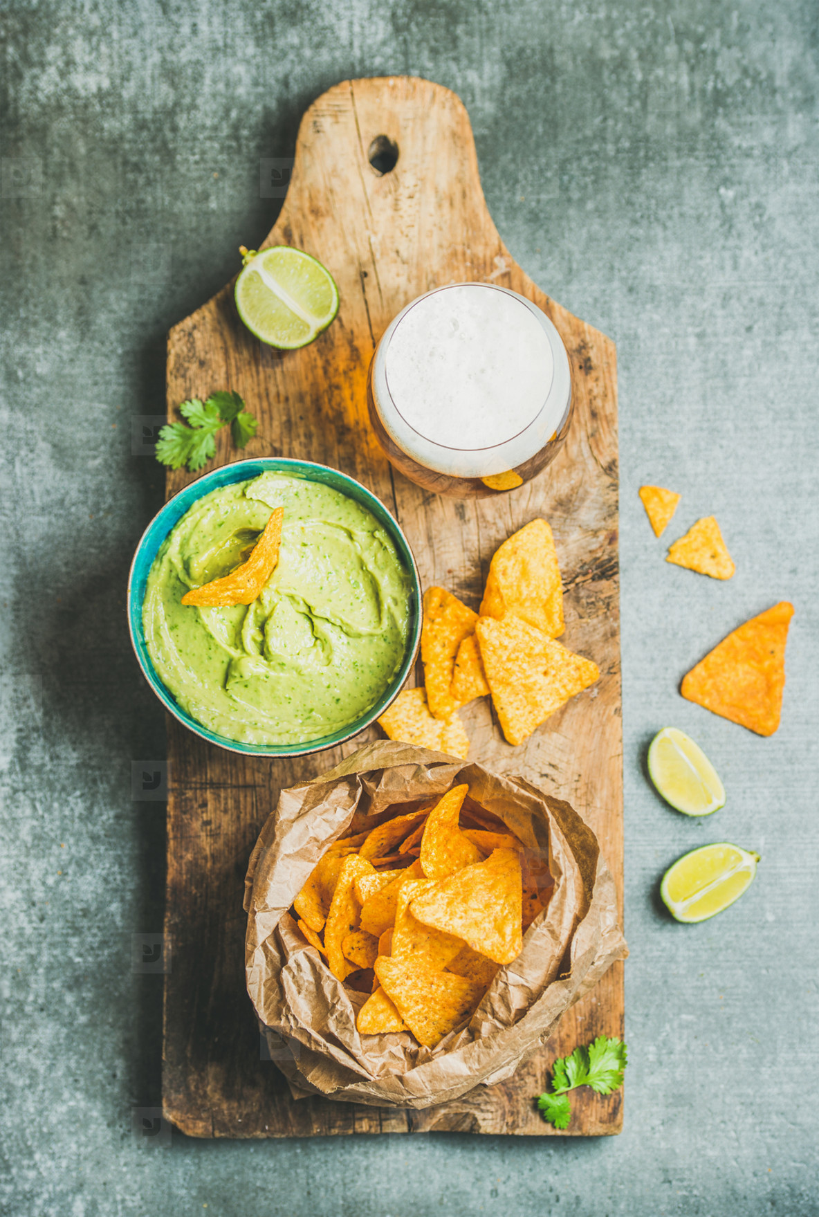 Mexican corn chips  fresh guacamole sauce and beer  wooden board