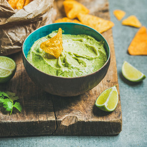 Fresh guacamole sauce in blue bowl and chips  square crop