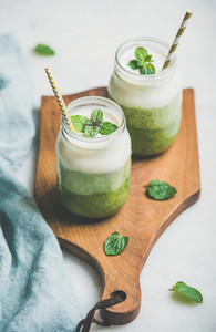 Ombre layered green smoothies in glass jars with straws
