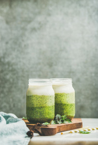Ombre layered green smoothies with fresh mint in glass jars