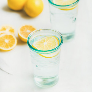 Morning detox lemon water in glasses served with fresh lemons