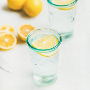 Morning detox lemon water in glasses served with fresh lemons