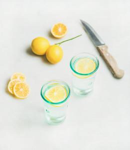 Morning detox lemon water in glasses over marble background