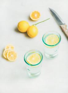 Morning detox lemon water in glasses over light marble background