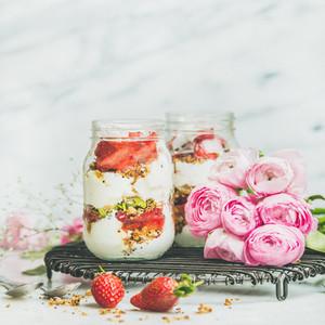 Healthy spring breakfast jars with pink raninkulus flowers  square crop