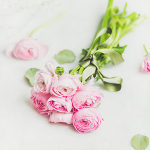 Light pink spring ranunkulus flowers bouquet on white marble background