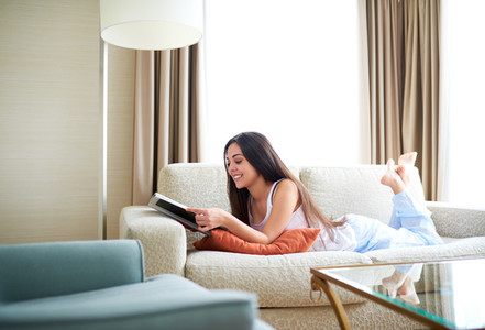 Side view of woman lying on couch reading