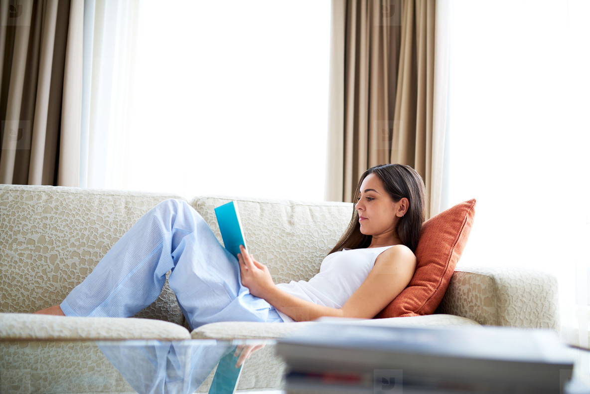 Woman reclining against orange cushion on couch