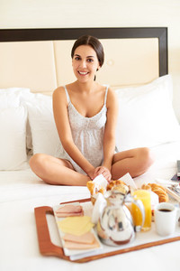 Woman relaxing in bed with breakfast tray
