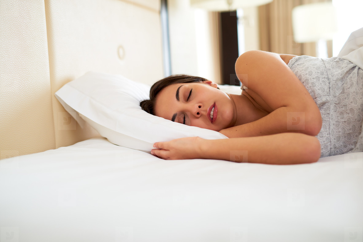 Woman sleeping in bed on her side
