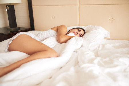 Woman lying on her side in bed hugging duvet