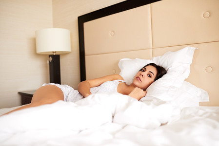 Woman lying in bed looking at camera