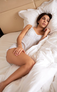 Woman lying in bed with hand on thigh