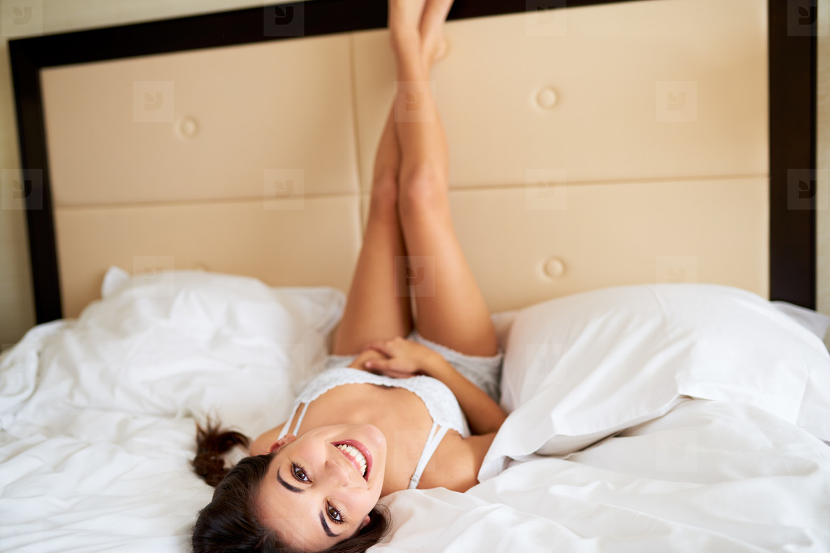 Woman lying upside down with legs against headboard