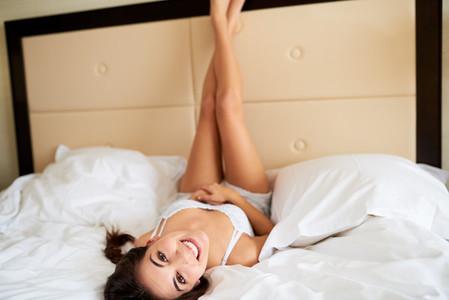 Woman lying upside down with legs against headboard