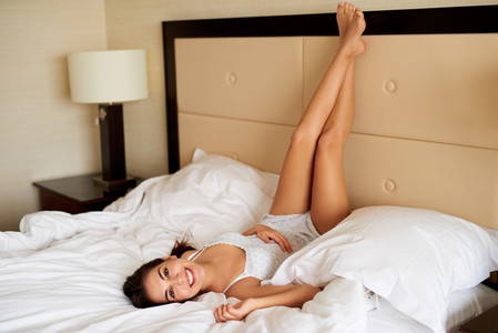 Woman lying upside down on bed smiling at camera
