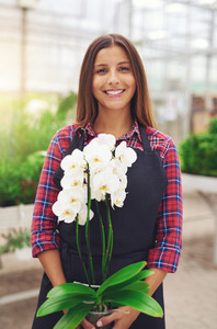 Smiling young florist holding an orchid